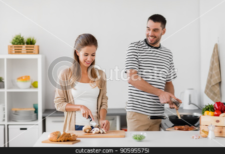 couple cooking food at home kitchen stock photo, people and healthy eating concept - couple cooking food at home kitchen by Syda Productions