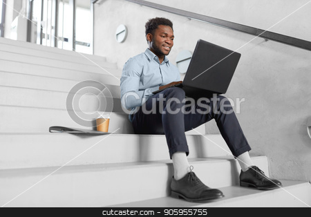 african american businessman with laptop at office stock photo, business, people and technology concept - african american businessman with laptop working computer at office stairs by Syda Productions