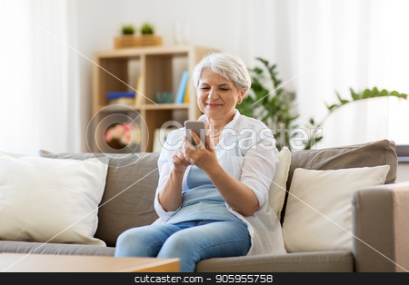 happy senior woman with smartphone at home stock photo, technology, communication and people concept - happy senior woman with smartphone at home by Syda Productions