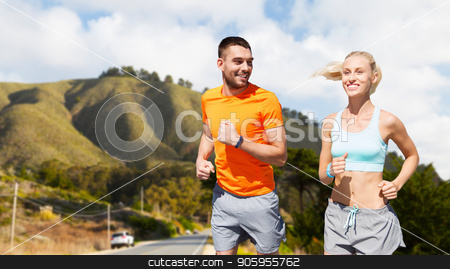 smiling couple running over big sur hills stock photo, fitness, sport and healthy lifestyle concept - smiling couple with heart-rate watch running over big sur hills and road background in california by Syda Productions