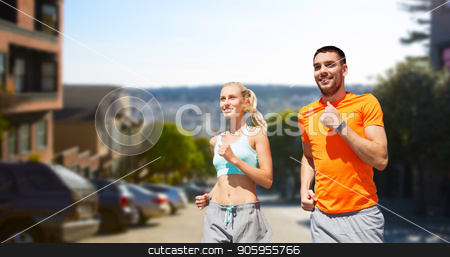 smiling couple running over san francisco city stock photo, fitness, sport and healthy lifestyle concept - smiling couple with heart-rate watch running over san francisco city background by Syda Productions