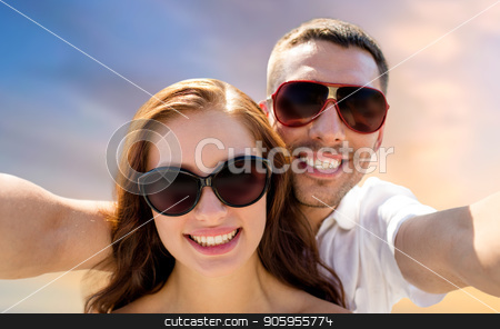 smiling couple wearing sunglasses making selfie stock photo, love, summer and people concept - smiling couple wearing sunglasses making selfie over evening sky background by Syda Productions