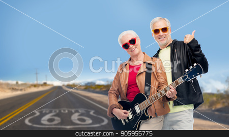 senior couple with guitar over route 66 stock photo, rock music, old age and travel concept - happy senior couple with electric guitar over us route 66 background showing thumbs up by Syda Productions