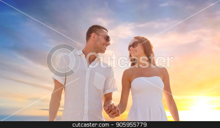 happy couple holding hands over sunset sky stock photo, love, summer and relationships concept - happy couple on vacation wearing sunglasses walking and holding hands over sunset sky background by Syda Productions