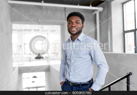 smiling african american businessman at office stock photo, business and people concept - smiling african american businessman at office by Syda Productions
