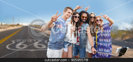 hippie friends taking selfie over us route 66 stock photo, travel, technology and road trip concept - smiling young hippie friends taking picture by smartphone on selfie stick and showing peace hand sign over us route 66 background by Syda Productions