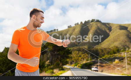 man with smart watch or fitness tracker stock photo, sport, technology and healthy lifestyle concept - smiling young man with smart watch or fitness tracker over big sur hills and road background in california by Syda Productions