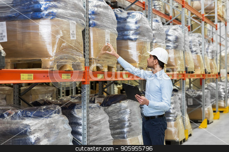 businessman with clipboard at warehouse stock photo, wholesale, logistic, business, export and people concept - man or manager in helmet with clipboard checking goods at warehouse by Syda Productions