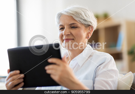 happy senior woman with tablet pc at home stock photo, technology, age and people concept - happy senior woman with tablet pc computer at home by Syda Productions