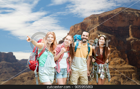 group of friends with backpacks at grand canyon stock photo, travel, tourism, hike and adventure concept - group of smiling friends with backpacks pointing finger to something over grand canyon national park background by Syda Productions