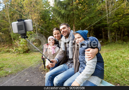 family taking photo by selfie stick outdoors stock photo, family, tourism and technology concept - happy mother, father, son and daughter taking picture by smartphone on selfie stick in woods by Syda Productions