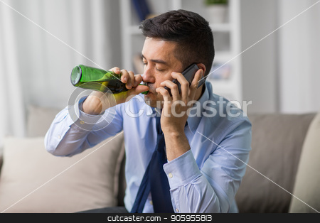 man drinking alcohol and calling on smartphone stock photo, alcoholism, alcohol addiction and people concept - male alcoholic drinking beer and calling on smartphone at home by Syda Productions