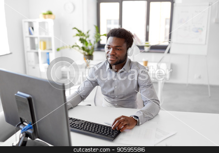 businessman with headphones and computer at office stock photo, business, technology and people concept - happy african american businessman with headphones and computer listening to music at office by Syda Productions