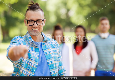 group of happy international friends outdoors stock photo, people, friendship and gesture concept - happy smiling man in glasses pointing at you and group of happy friends outdoors by Syda Productions