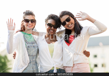 happy young women in sunglasses outdoors stock photo, female friendship, summer and eyewear - happy young women in sunglasses outdoors waving hands by Syda Productions