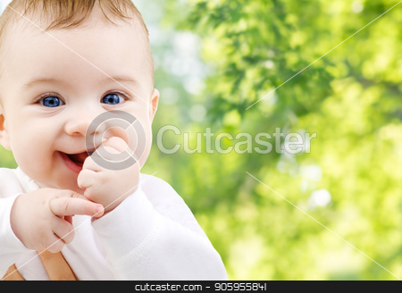 close up of sweet little baby stock photo, childhood and people concept - close up of sweet little baby over green natural background by Syda Productions