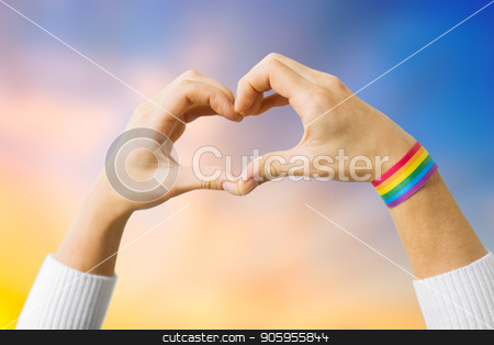 woman with gay awareness wristband showing heart stock photo, homosexual and lgbt concept - close up of woman wearing gay pride awareness ribbon wristband showing hand heart over evening sky background by Syda Productions