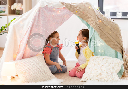 little girls with torch light in kids tent at home stock photo, childhood, hygge and friendship concept - little girls with torch light having fun in kids tent or teepee at home by Syda Productions