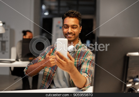 man with smartphone having video call at office stock photo, technology, communication and deadline concept - creative man with smartphone and computer having video call at night office and showing thumbs up by Syda Productions