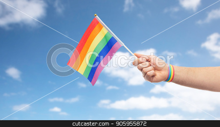 hand with gay pride rainbow flag and wristband stock photo, lgbt, same-sex relationships and homosexual concept - close up of male hand with gay pride awareness wristband holding rainbow flag over blue sky and clouds background by Syda Productions