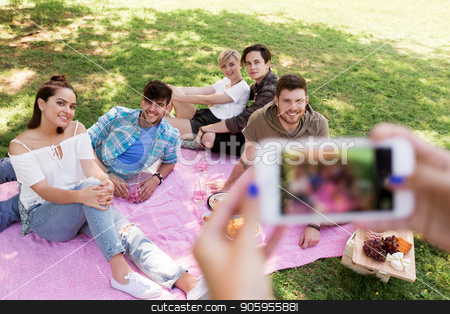 friends photographing by smartphone at picnic stock photo, friendship, leisure and technology concept - group of happy smiling friends with non alcoholic drinks taking picture by smartphone on picnic at summer park by Syda Productions