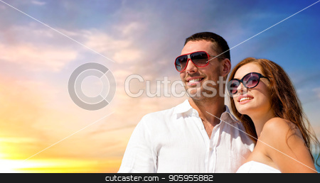 happy smiling couple in sunglasses stock photo, love, summer and relationships concept - happy smiling couple in sunglasses over evening sky background by Syda Productions