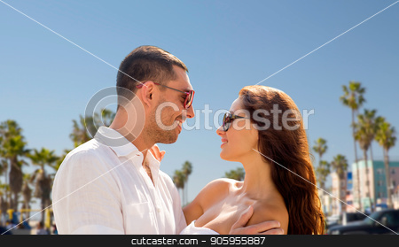 happy couple in sunglasses over venice beach stock photo, travel, tourism and relationships concept - happy smiling couple in sunglasses hugging over venice beach background in california by Syda Productions