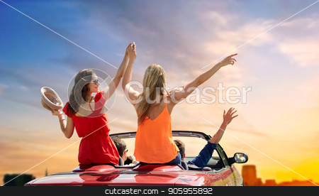 friends driving in convertible car over sunset stock photo, summer holidays, road trip and travel concept - happy friends driving in convertible car at country and waving hands over sky background by Syda Productions