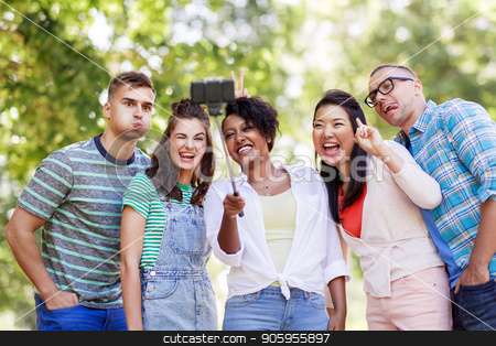 international friends taking selfie in park stock photo, people, friendship and international concept - happy smiling young woman and group of happy friends taking picture by selfie stick in park by Syda Productions