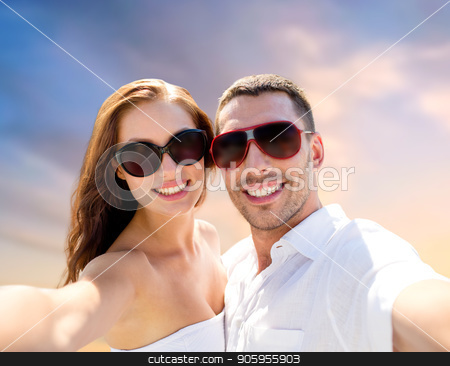smiling couple in sunglasses making selfie stock photo, love, summer and people concept - smiling couple wearing sunglasses making selfie over evening sky background by Syda Productions