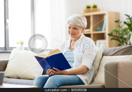 happy smiling senior woman reading book at home stock photo, age, leisure and people concept - happy smiling senior woman reading book at home by Syda Productions