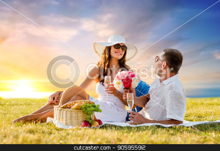 couple with flowers drinking champagne at picnic stock photo, love, dating, people and celebration concept - smiling couple with flowers drinking champagne at picnic on meadow over sunset sky background by Syda Productions