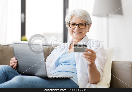 senior woman with laptop and credit card at home stock photo, technology, online shopping and people concept - happy senior woman in glasses with laptop computer and credit or bank card at home by Syda Productions