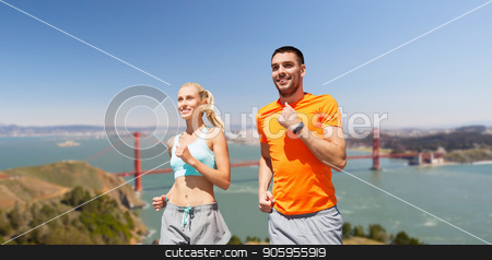 happy couple running over golden gate bridge stock photo, fitness, sport and healthy lifestyle concept - smiling couple with heart-rate watch running over golden gate bridge in san francisco bay background by Syda Productions