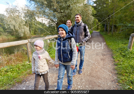 family with backpacks hiking or walking in woods stock photo, family, tourism and hiking concept - happy mother, father, son and daughter with backpacks walking in woods by Syda Productions