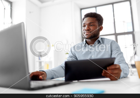 businessman with laptop and tablet pc at office stock photo, business, people and technology concept - african american businessman with laptop and tablet pc computer at office by Syda Productions