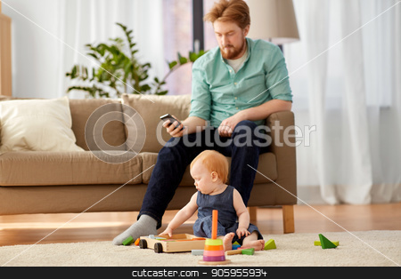 father and baby playing with toy blocks at home stock photo, family, fatherhood and people concept - happy red haired father with smartphone and little baby daughter playing with toy blocks kit at home by Syda Productions