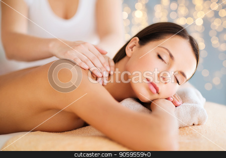 close up of beautiful woman having massage at spa stock photo, wellness, spa and beauty concept - close up of beautiful woman having massage over holidays lights background by Syda Productions
