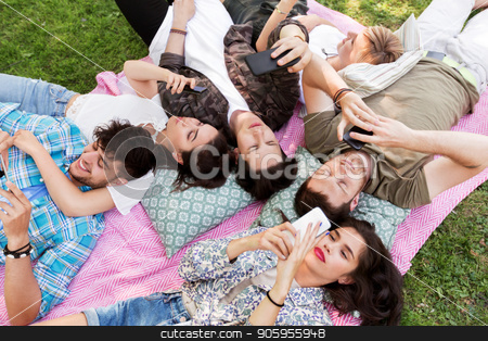 friends with smartphones on picnic blanket stock photo, friendship, leisure, technology and people concept - group of friends with smartphones chilling on picnic blanket at summer park by Syda Productions