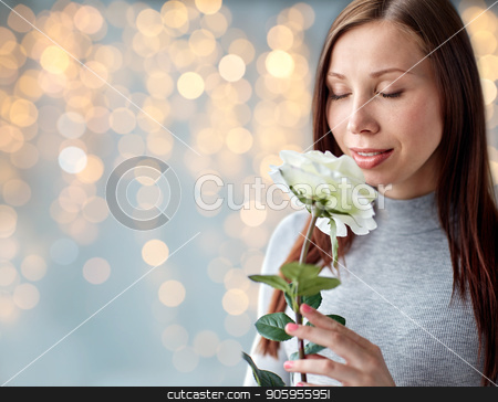 woman smelling white rose over festive lights stock photo, people and flowers concept - happy young woman smelling big white rose over festive lights background by Syda Productions