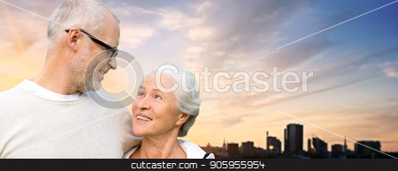 senior couple hugging over evening tallinn city stock photo, old age, tourism, travel and people concept - happy senior couple hugging over tallinn city and evening sky background by Syda Productions