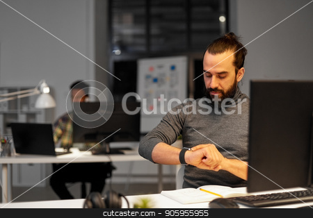 creative man with smartwatch at night office stock photo, deadline, technology and people concept - creative man with smartwatch and computer working late at night office by Syda Productions