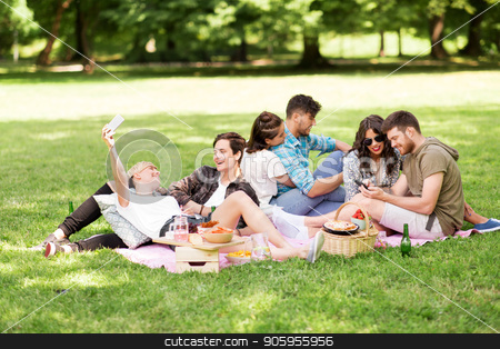 friends with smartphones on picnic at summer park stock photo, friendship, leisure, technology and people concept - group of friends with smartphones and non alcoholic beer chilling on picnic blanket at summer park by Syda Productions