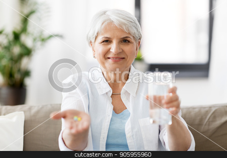 senior woman with water and medicine at home stock photo, age, medicine, healthcare and people concept - senior woman with pills and glass of water at home by Syda Productions