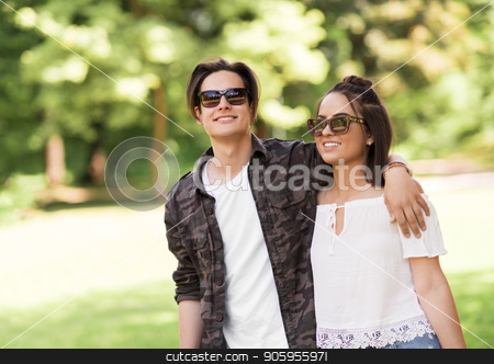happy couple in sunglasses hugging at summer park stock photo, people and leisure concept - happy couple in sunglasses hugging at summer park by Syda Productions