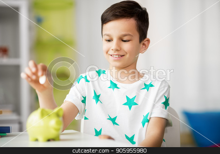 little boy putting coin into piggy bank at home stock photo, money, finances, childhood and people concept - smiling little boy putting coin into piggy bank at home by Syda Productions