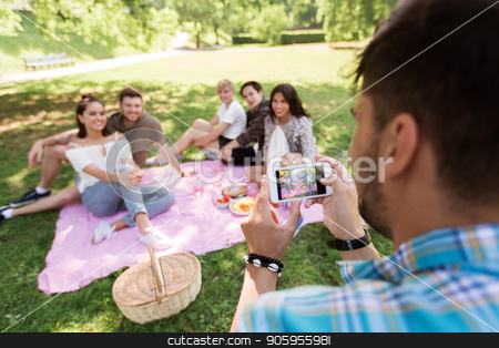 man photographing friends by smartphone at picnic stock photo, friendship, leisure and technology concept - man taking picture of his friends by smartphone on picnic at summer park by Syda Productions