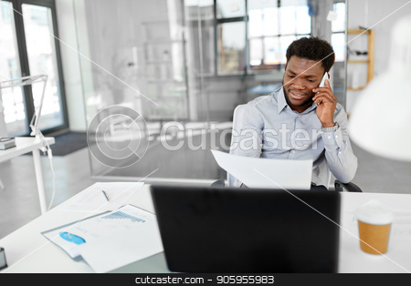 businessman calling on smartphone at office stock photo, business, people, communication and technology concept - smiling african american businessman with papers and laptop computer calling on smartphone at office by Syda Productions