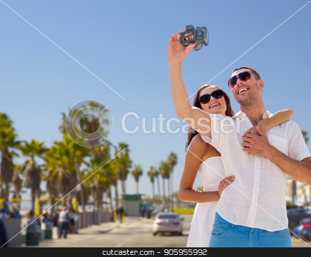 couple making selfie by camera over venice beach stock photo, travel, tourism, summer and technology concept - smiling couple in sunglasses making selfie by digital camera over venice beach background in california by Syda Productions
