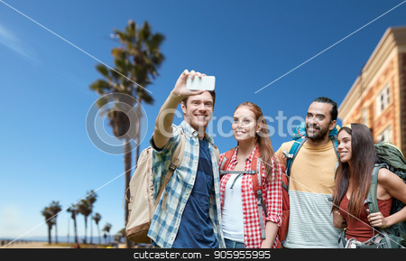 friends with backpack taking selfie by smartphone stock photo, technology, travel, tourism, hike and people concept - group of smiling friends with backpacks taking selfie by smartphone over venice beach background in california by Syda Productions